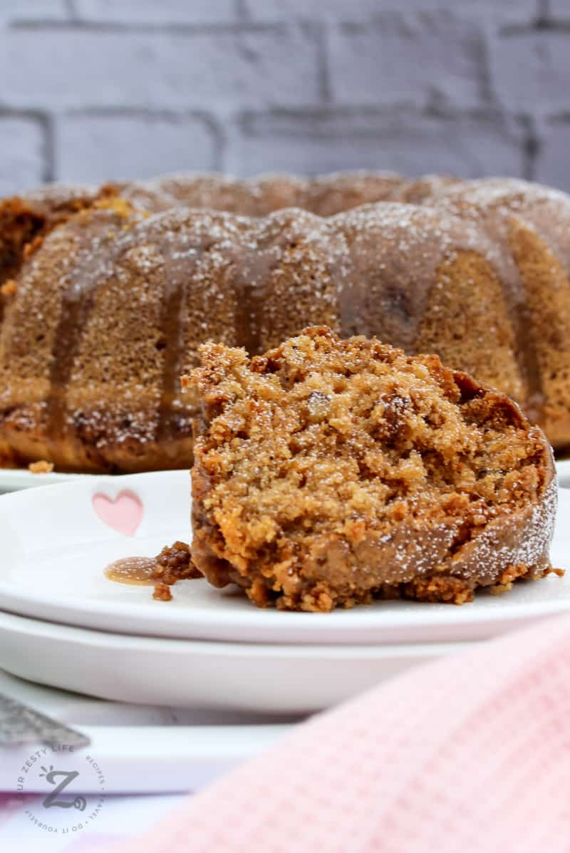a slice of apple bundt cake served on a white dish with the whole apple spice bundt cake in the background (side view)