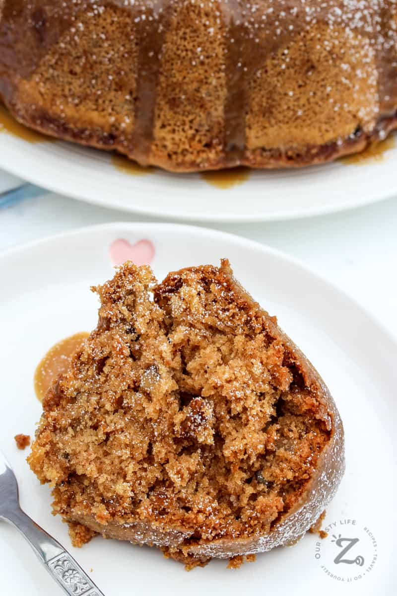 a slice of apple bundt cake served on a white dish with the whole apple spice bundt cake in the background