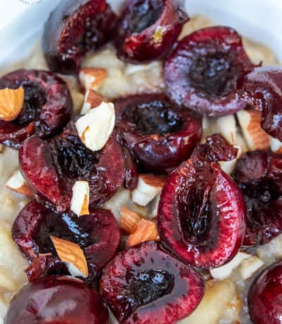 overhead view of pitted cherries sliced in half on top of almond milk oatmeal in a bowl