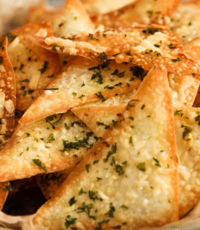 A close up of baked parmesan and parsley wonton crackers in a bowl.