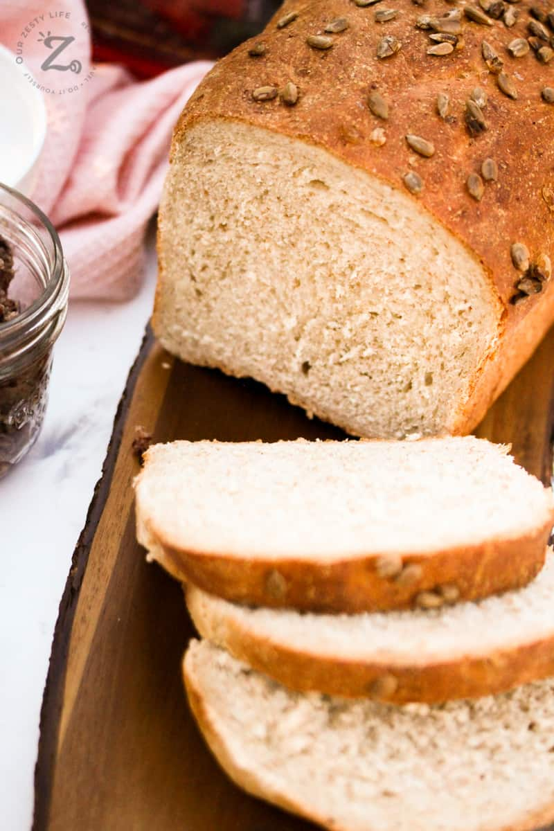 A loaf of whole wheat bread with three slices cut from it and strawberry butter beside the loaf.