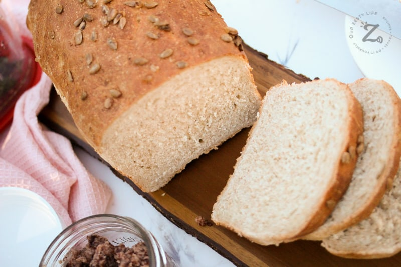 A loaf of whole wheat bread with a three slices cut from it and strawberry butter beside the loaf.
