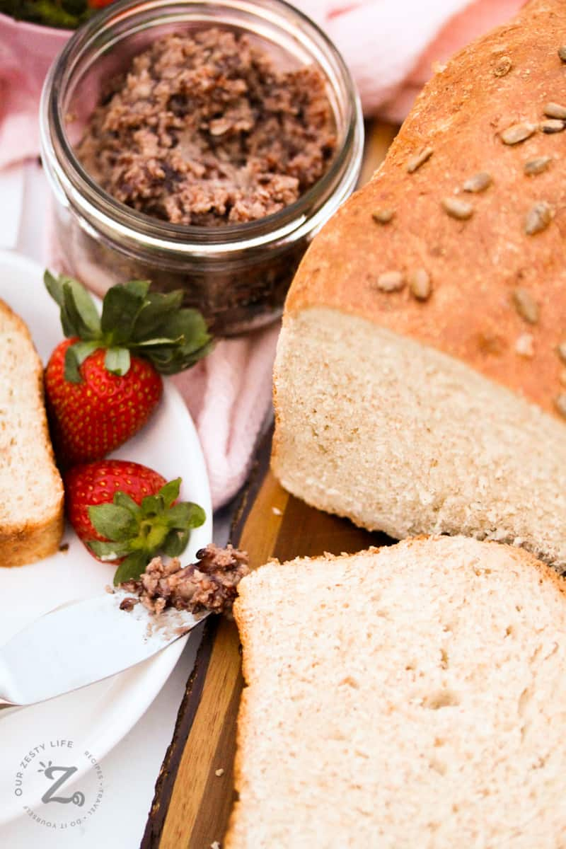 A loaf of whole wheat bread with a slice cut from it and strawberry butter beside the loaf.