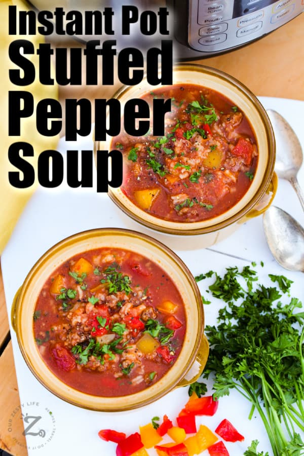Two bowls of Instant Pot stuffed pepper soup on a cutting board.
