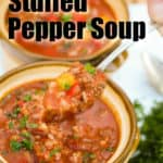 A close up of a spoonful of Instant Pot stuffed pepper soup held over top of a bowl f stuffed pepper soup and another bowl in the background.