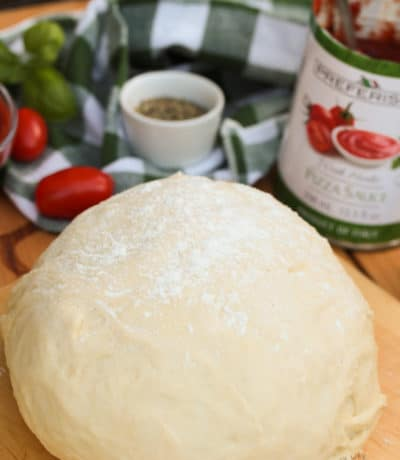 A ball of homemade pizza dough on a rolling board sprinkled with flour.