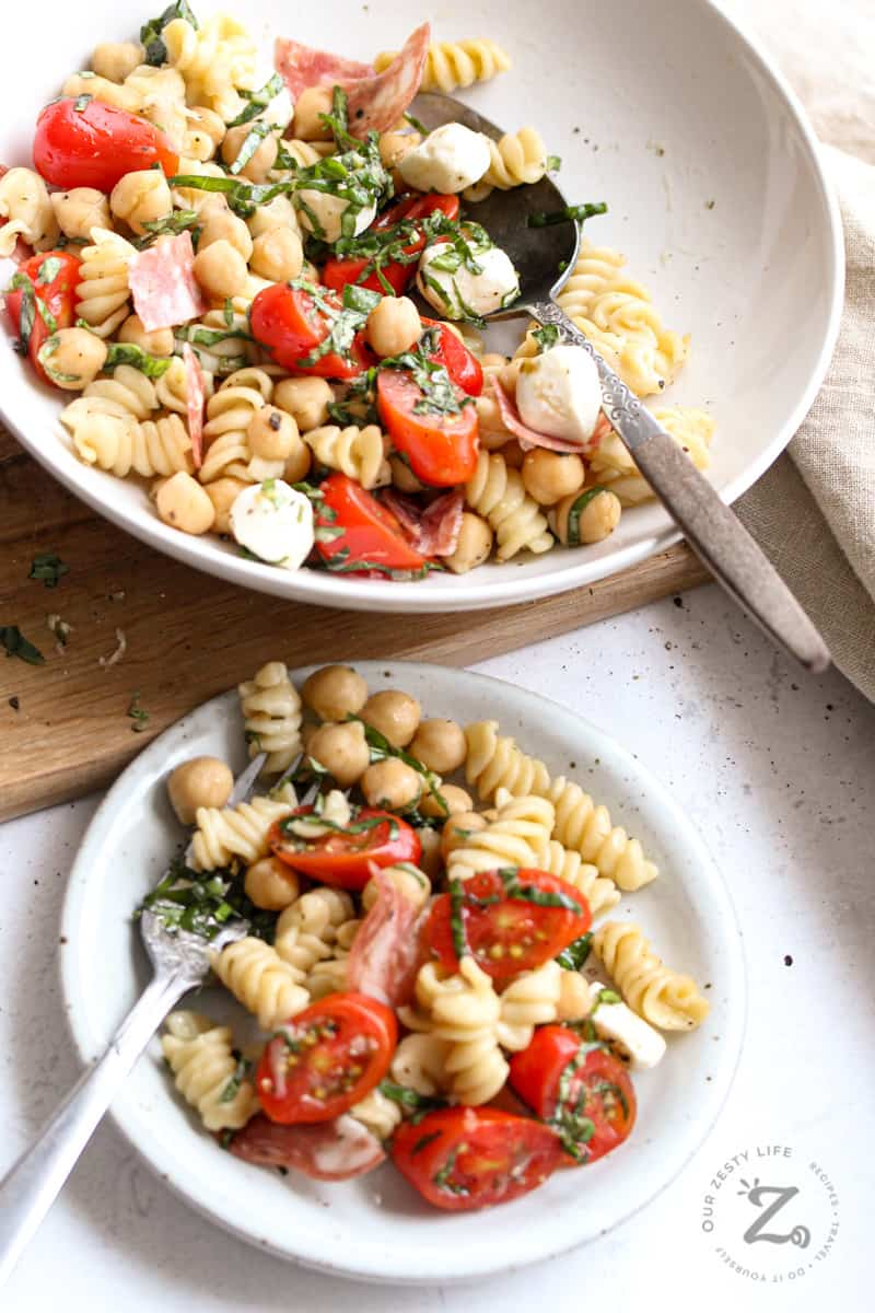 a small plate with chickpea pasta salad along with a serving bowl full of the salad, with tomatoes, bocconcini, salami and basil
