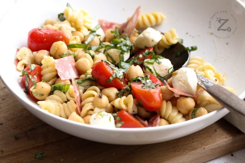 A close up of chickpea pasta salad in a white bowl with a spoon