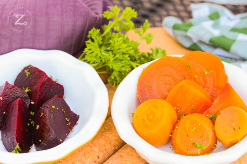 a close up of yellow beets on a white plate and a plate of red beets in the background