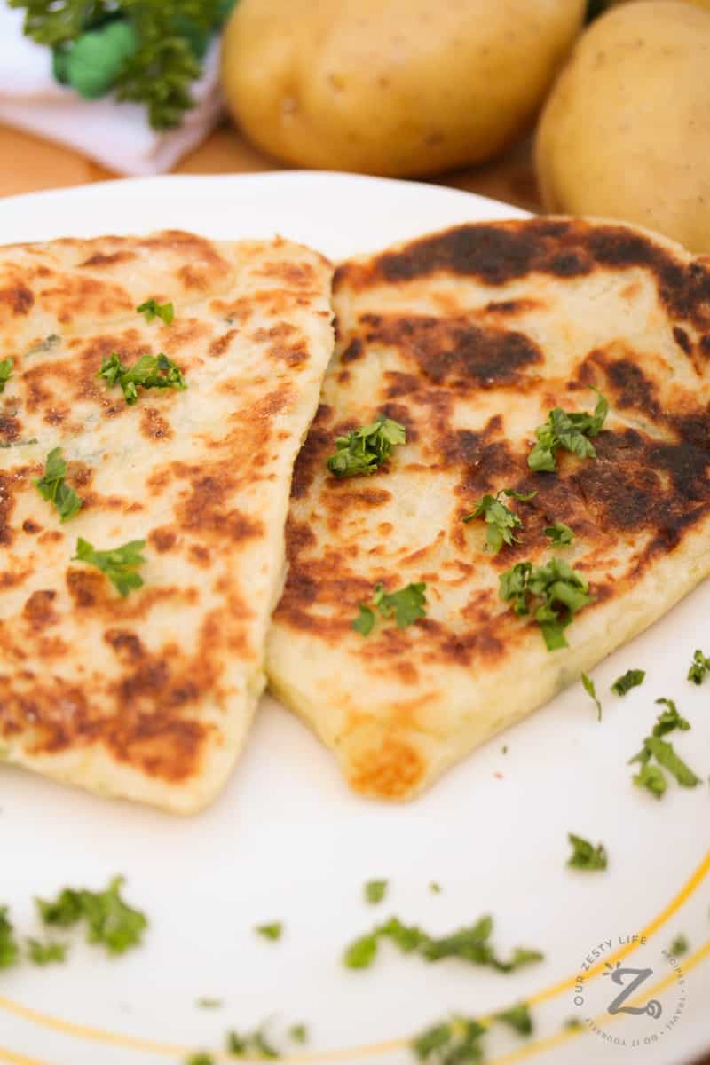 two Leftover mashed potato pancakes on a white plate with parsley