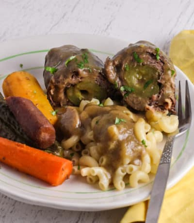 A serving of beef rouladen with macaroni and rainbow carrots