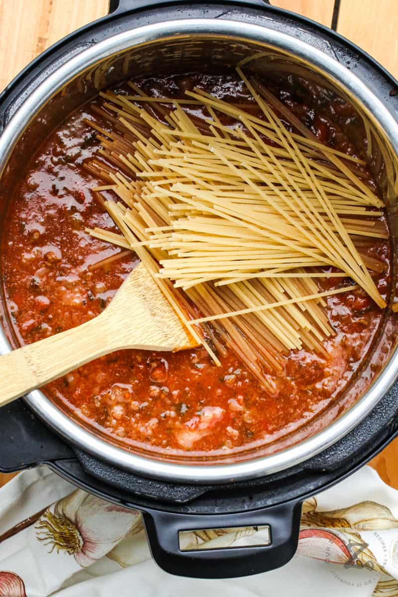 Instant Pot Bolognese with noodles and a wooden spoon