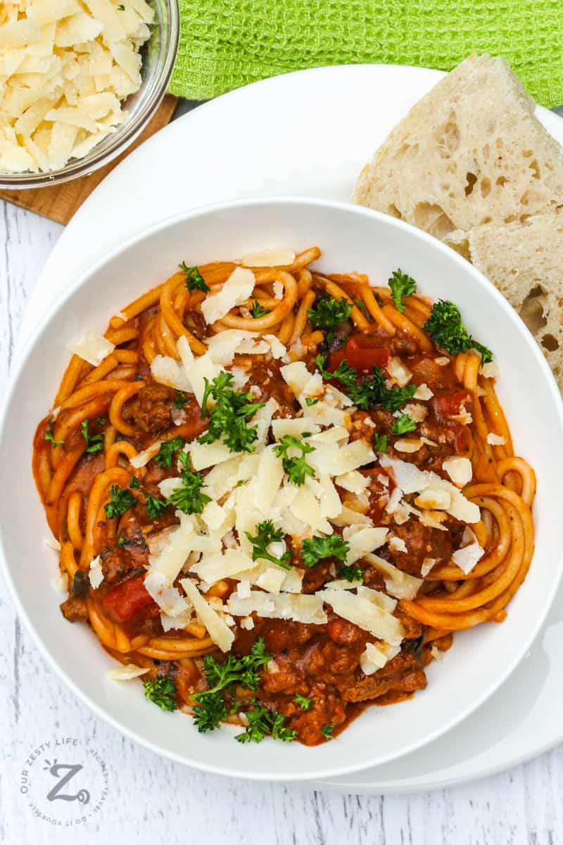 Instant Pot Bolognese in a white bowl with parmesan cheese and parsley as garnish