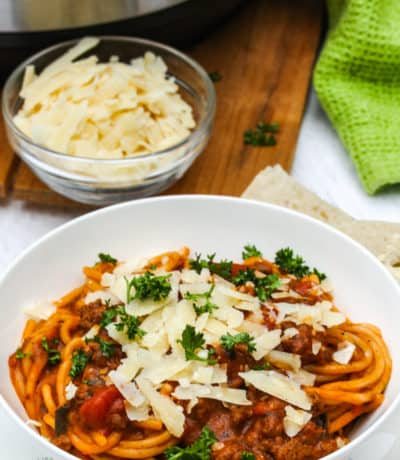 Instant Pot Bolognese in a white bowl with parmesan cheese and parsley