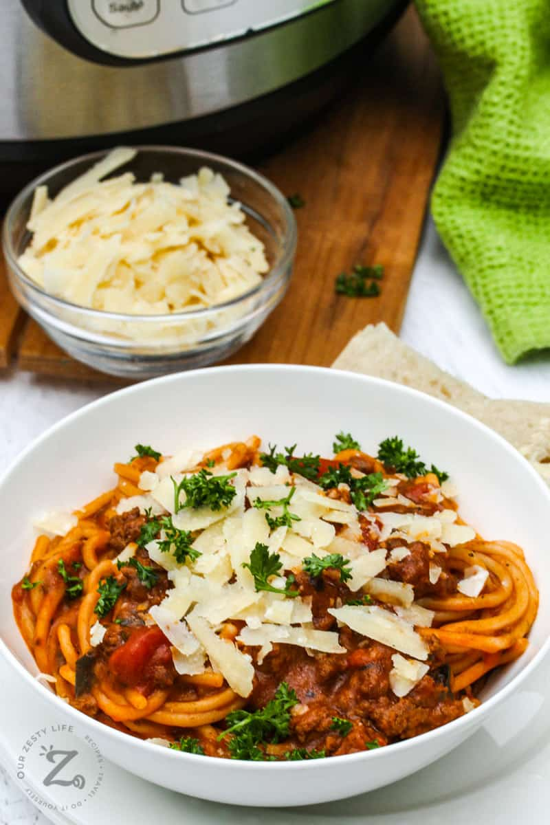 Instant Pot Bolognese in a white bowl with shaved parmesan cheese and parsley