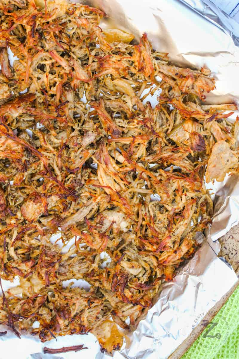 Pork Carnita meat on a baking sheet with tin foil