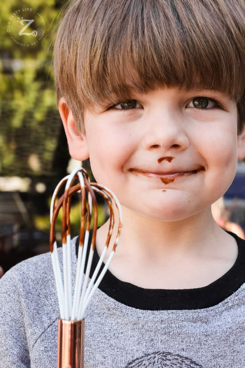 Boy licking the whisk for spicy chocolate sauce