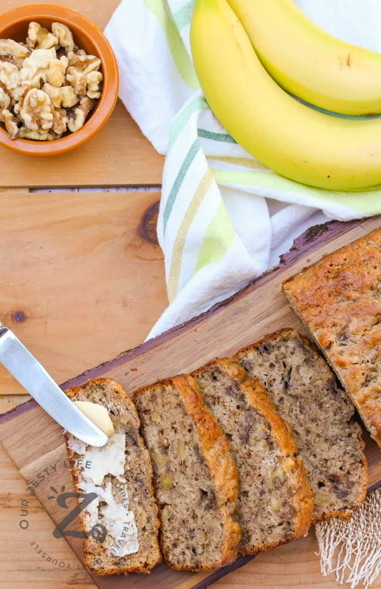 Slices of Banana Walnut Bread on a wooden board with bananas and walnuts on the side
