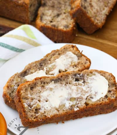 slices of Banana Walnut Bread on a plate with the loaf in the background