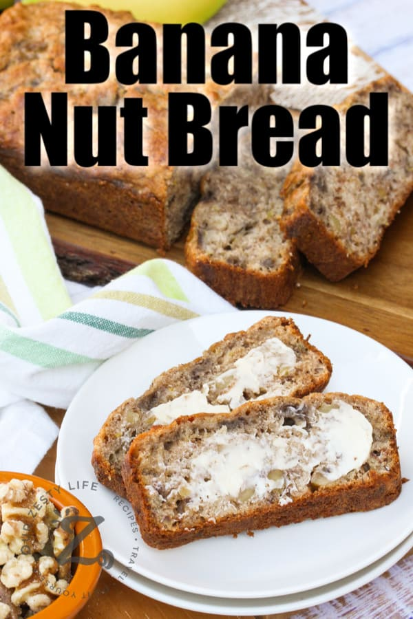 slices of Banana Walnut Bread on a plate with the loaf on the side with writing