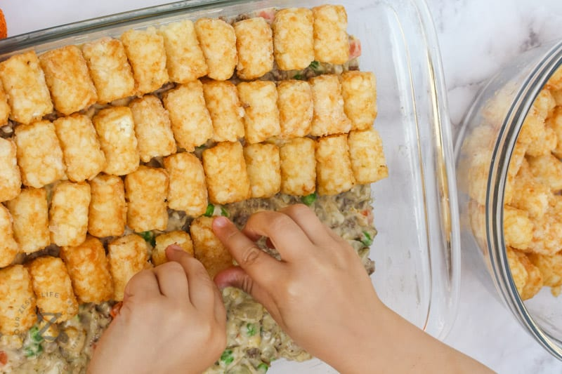 top view of tator tots being put on top of Cheesy Tater Tot Casserole