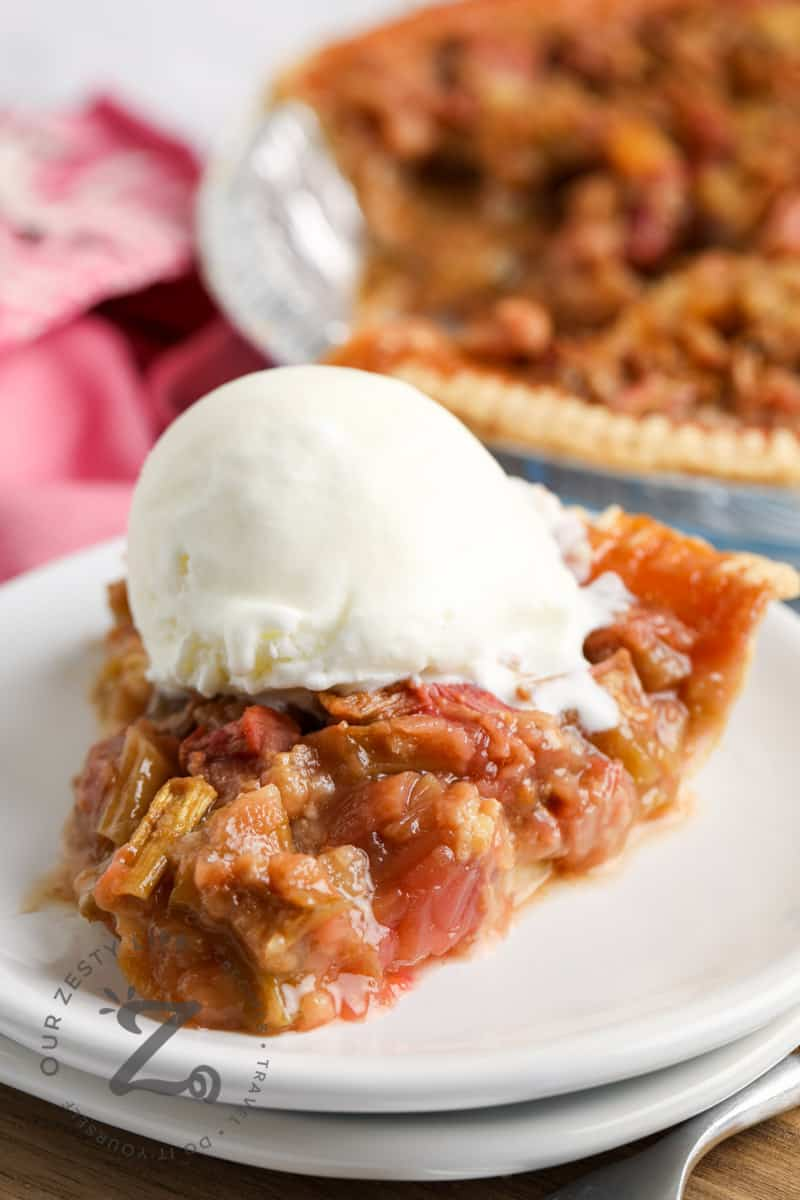 close up of Ginger Rhubarb Pie with a scoop of ice cream on a white plate