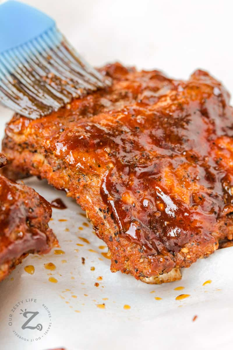Instant Pot Ribs getting brushed with sauce