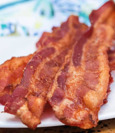close up of Bacon in the Oven on a white plate with a napkin