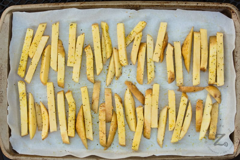 top view of cut potatoes on baking sheet to make Oven Baked Fries