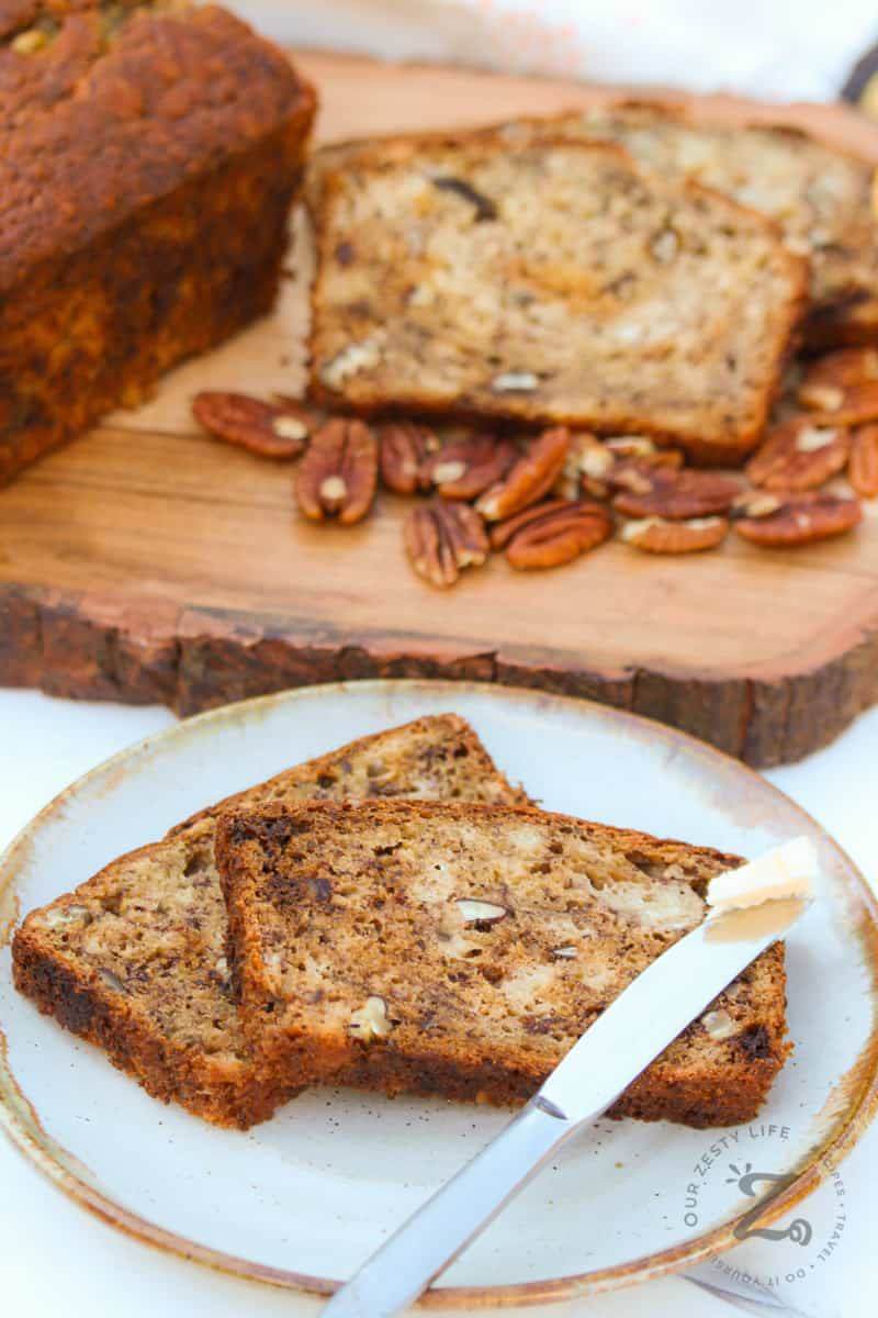 Simple Banana Bread sliced on a plate with a butter knife and loaf in the background