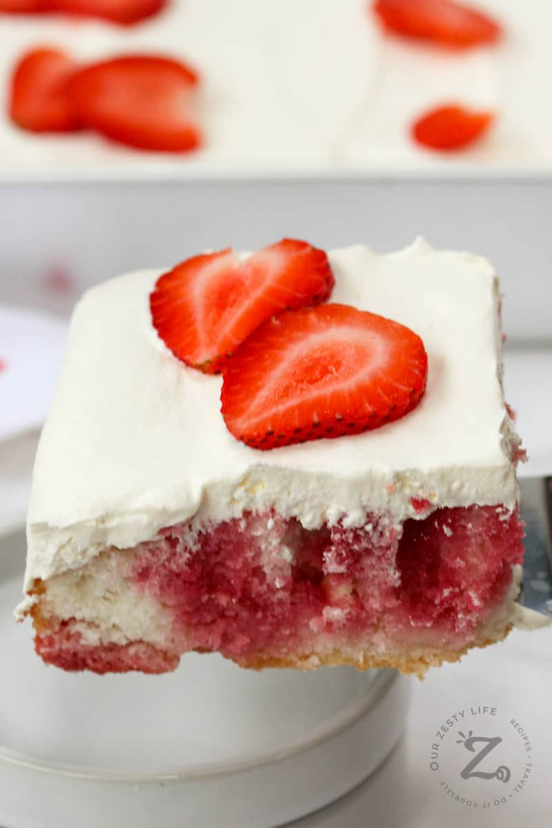 slice of Strawberry Poke Cake being put on a plate