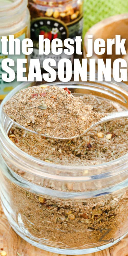 close up of spoonful of Jerk Seasoning Recipe with ingredients around it and a title