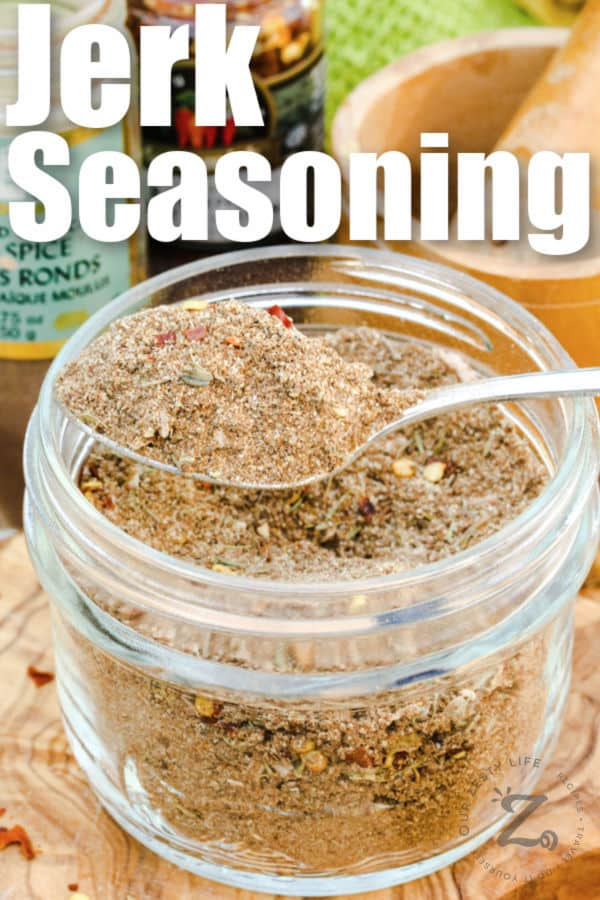 spoonful of Jerk Seasoning Recipe in a har with ingredients and a title