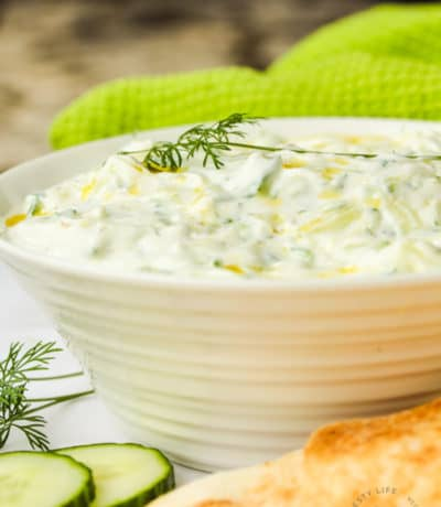 Tzatziki in a bowl with cucumber and pita beside it