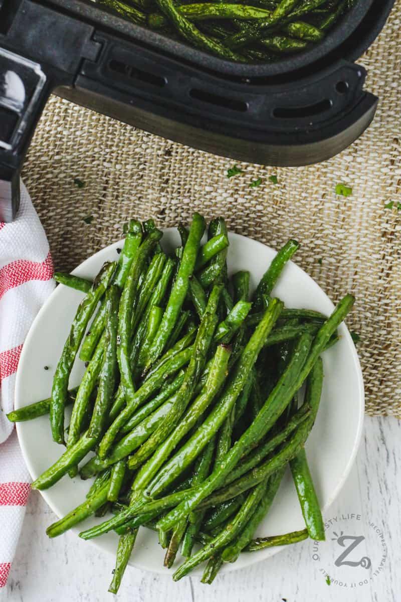 plated Air Fryer Green Beans with an air fryer full of beans
