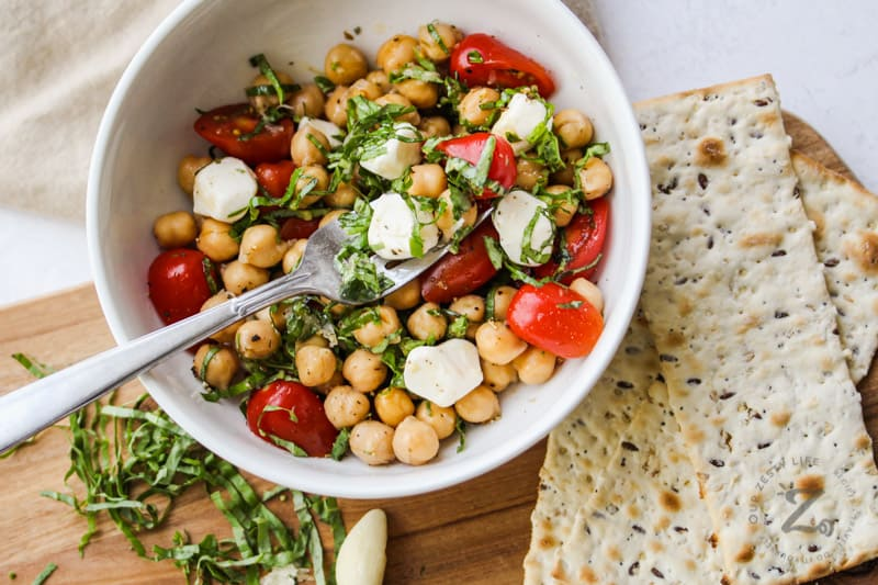 top view of Chick Pea Salad in a bowl with crackers beside it