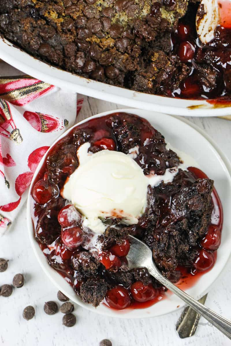 Chocolate Cherry Dump Cake on a plate with ice cream and a fork