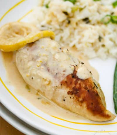cooked Creamy Lemon Chicken on a plate with a lemon