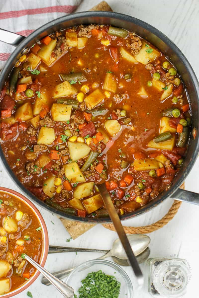 Hamburger Soup in a pot with a bowl beside it