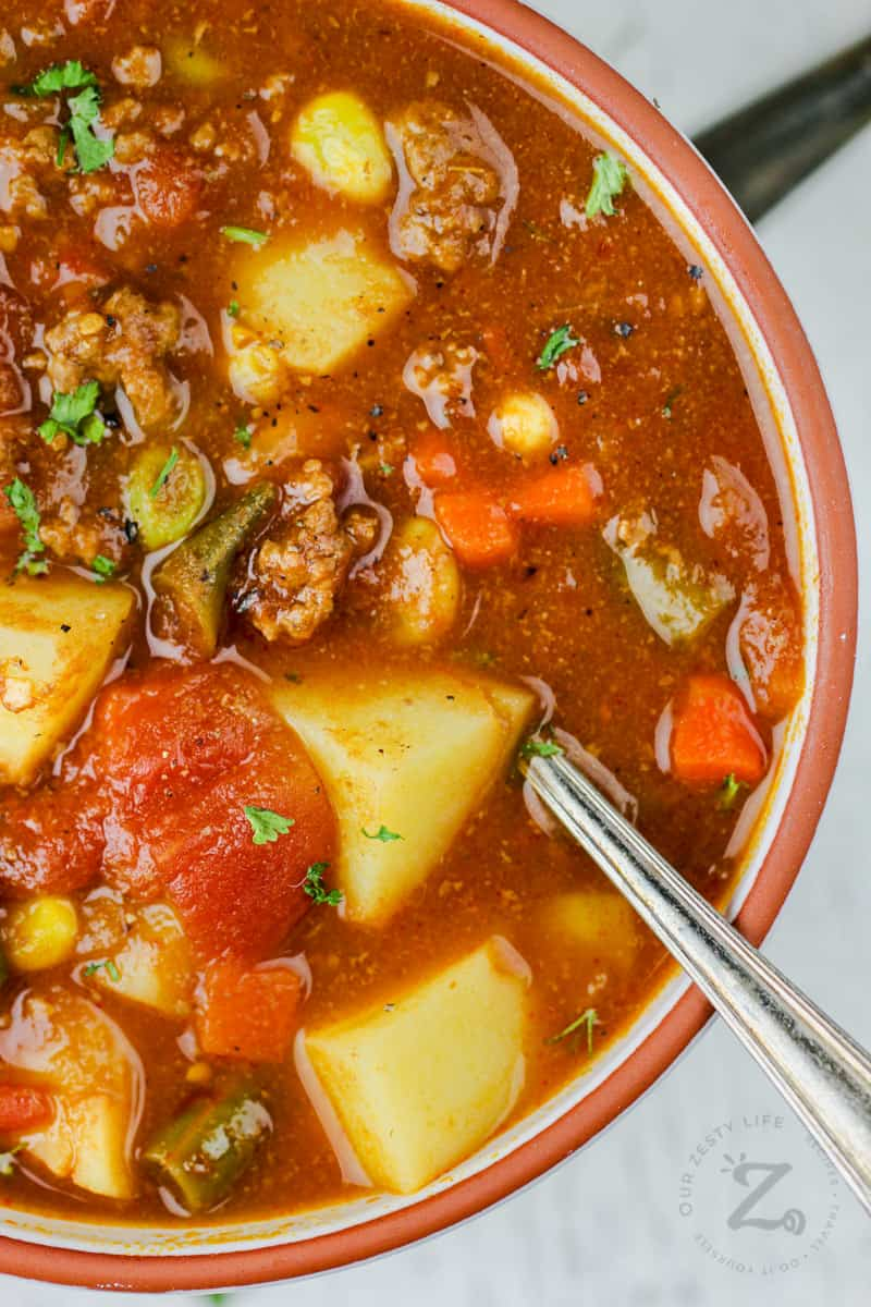 close up of Hamburger Soup in a bowl with a spoon