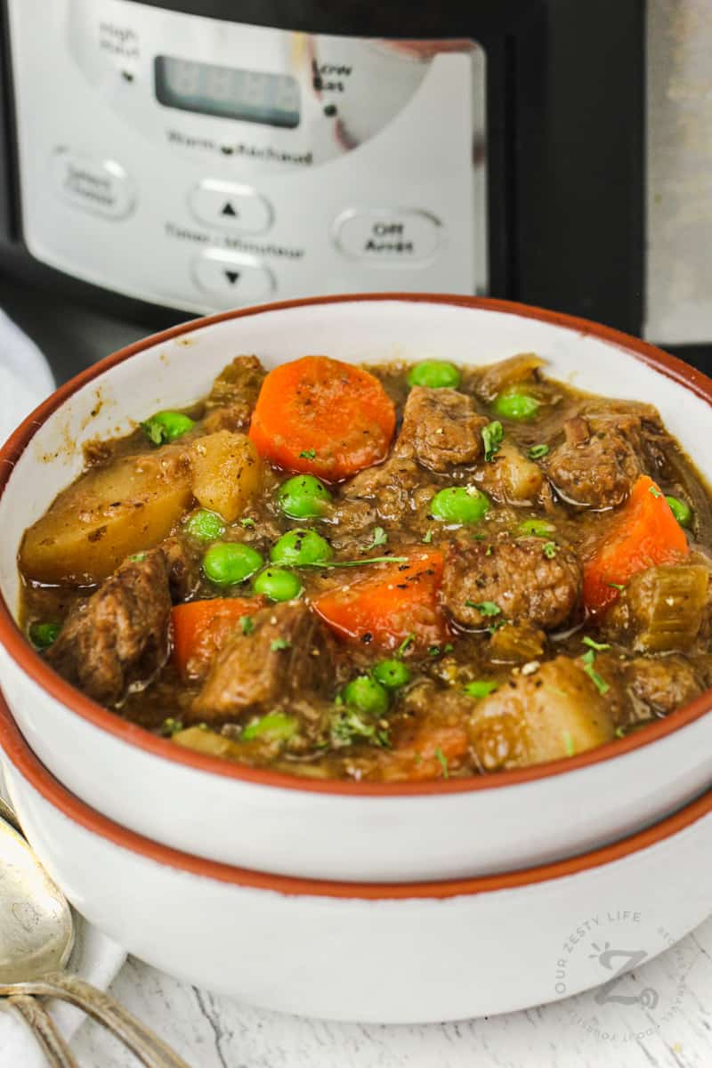 bowl of Beef Stew with crock pot in the background