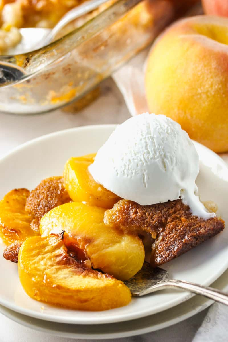 plated Peach Cobbler with the casserole dish in the back