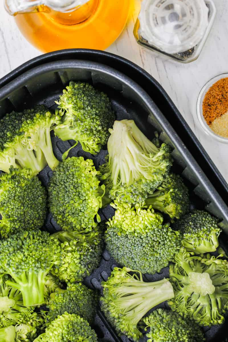 broccoli in the air fryer with seasonings around it to make Air Fryer Broccoli
