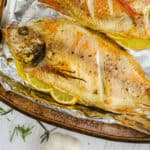 Baked Whole Fish cooked on a baking sheet with lemon garlic salt and seasonings