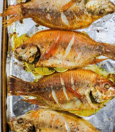 Baked Whole Fish in a row with lemon and seasonings