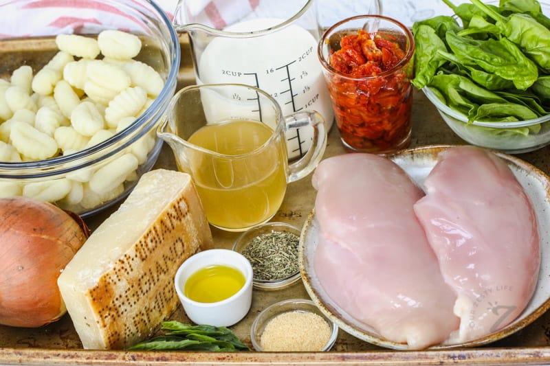 ingredients on a baking sheet to make Creamy Tuscan Chicken Gnocchi