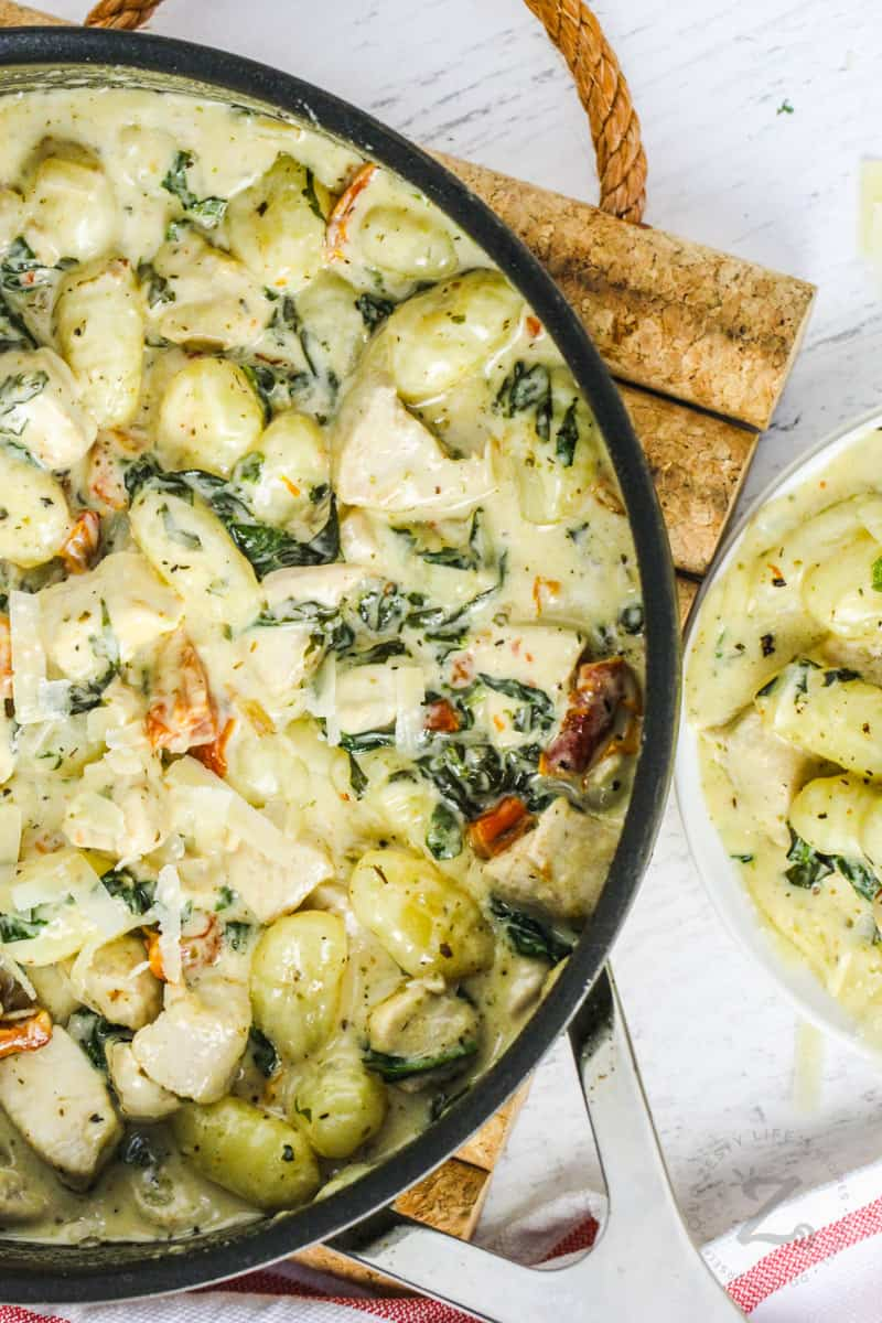 pot full of Creamy Tuscan Chicken Gnocchi with a plateful beside it
