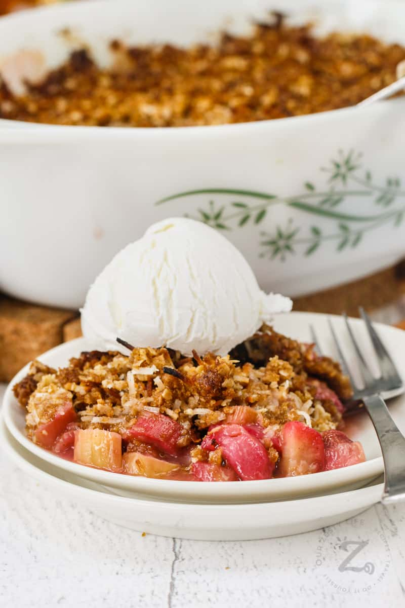 plated Rhubarb Crisp with ice cream and baking dish in the background