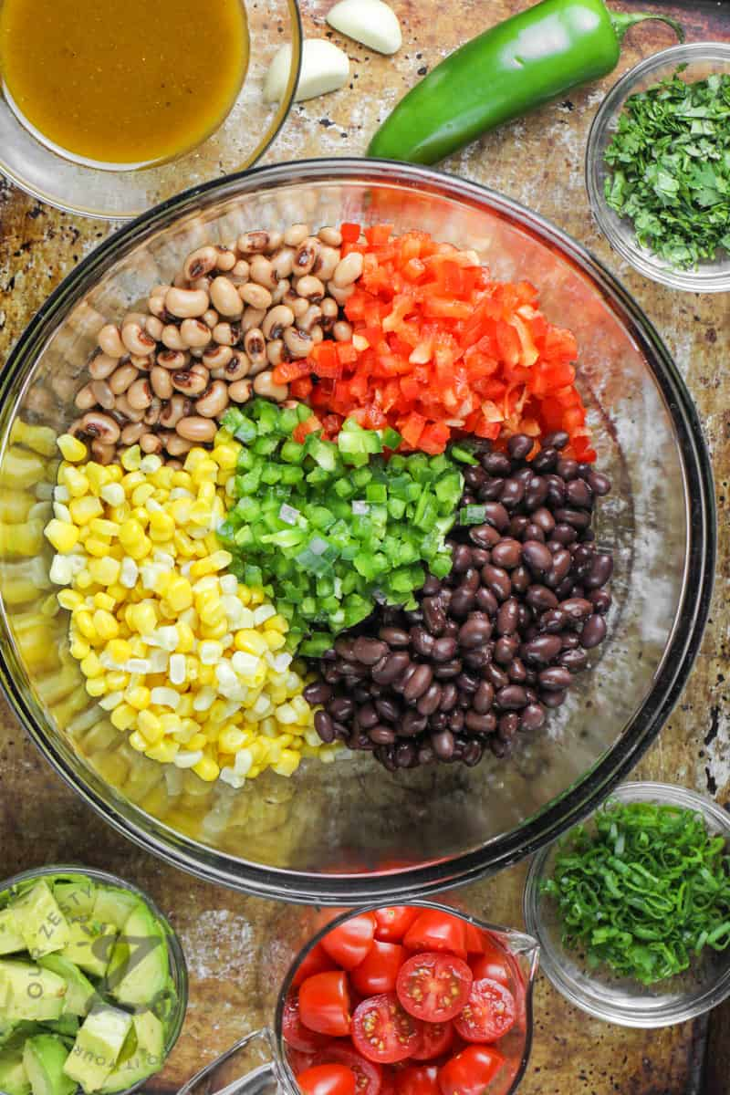 ingredients in a glass bowl to make Cowboy Caviar before mixing