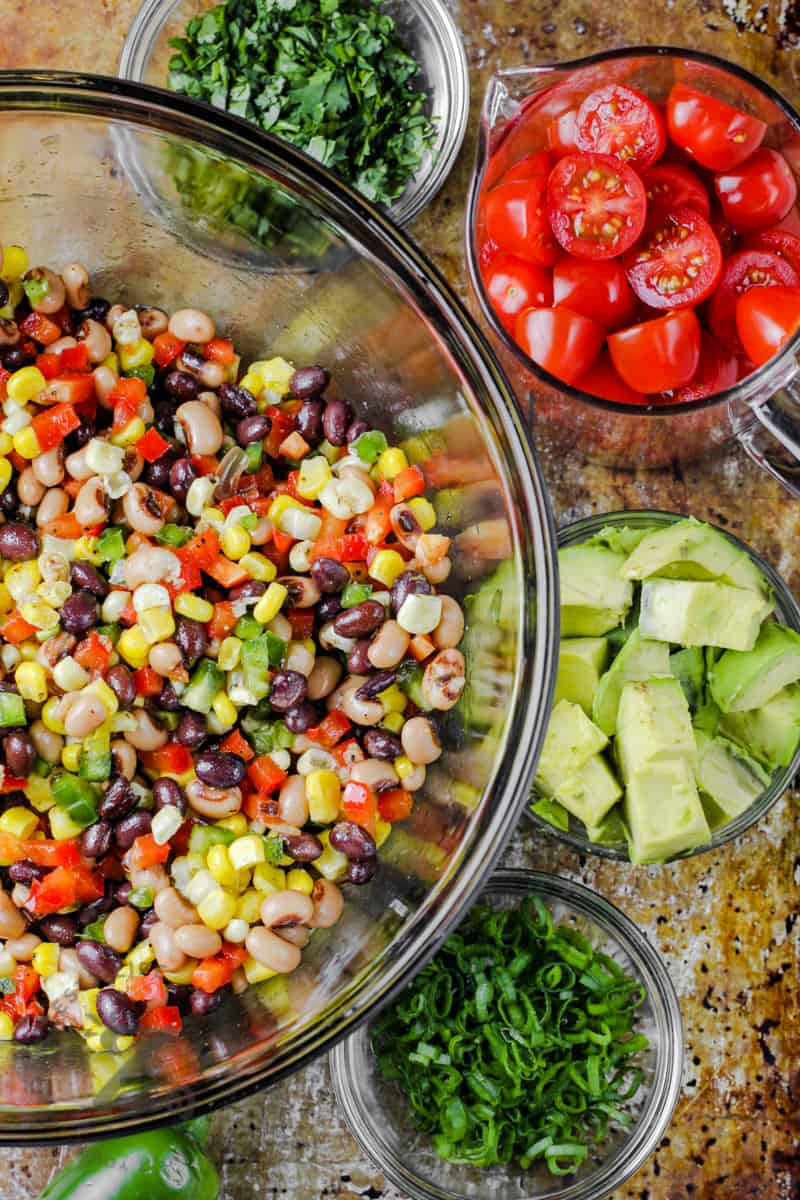 ingredients to make Cowboy Caviar in bowls and mixed salad